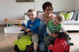 Eine Mutter spielt mit ihren zwei Kindern, welche auf einem Rutschauto sitzen.