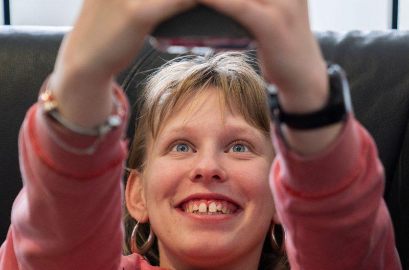 Une jeune femme avec un handicap mental est couchée sur un canapé et fait un selfie avec son téléphone.