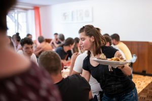 Eine Hotellerieangestellte mit geistiger Behinderung bedient die Gäste im Restaurant.