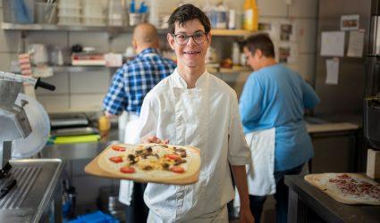 Un cuisinier en formation sert un repas.