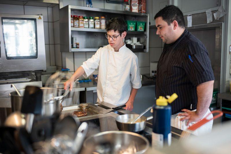 Un cuisinier et son apprenti en situation de handicap se tiennent debout dans la cuisine.