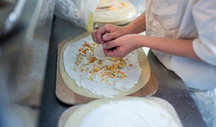 Un cuisinier en formation prépare une tarte flambée.