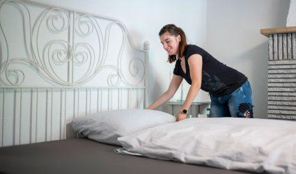 Une employée de La Demi-Lune fait le lit d'une des chambres de l'hôtel-restaurant.