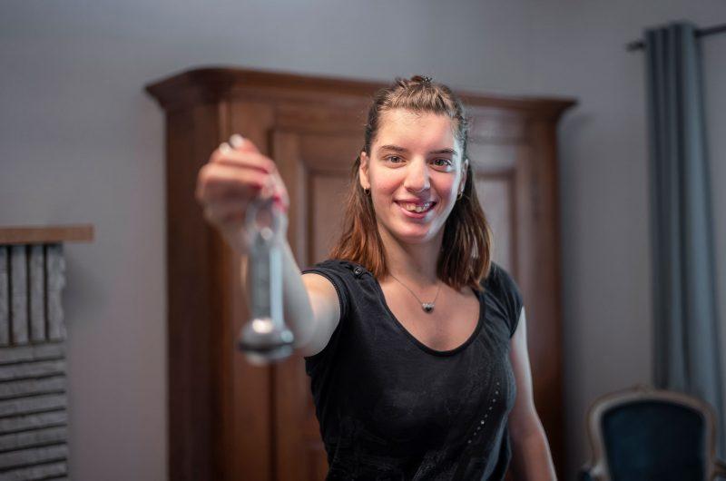 Une jeune femme tend une clé de chambre d'hôtel vers l'appareil photo.
