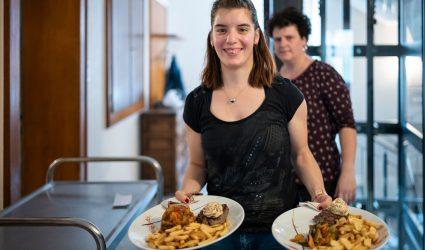 Une employée de l'hôtel-restaurant sert deux assiettes. En fond, on aperçoit la directrice.