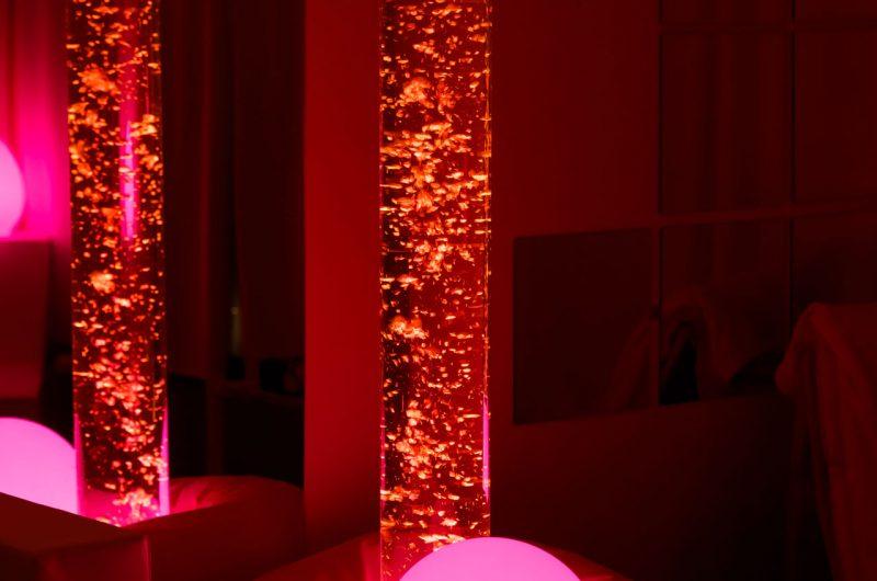 Deux colonnes à bulles sont illuminées dans une pièce sombre. Une lampe ronde enveloppée dans un nid de plume repose à leur pied