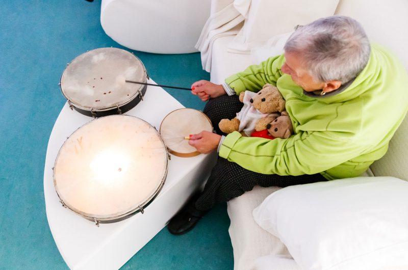 Hélène Delhayé frappe des tambourins, ses peluches posées sur les genoux
