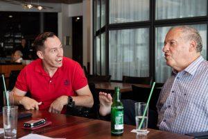 Islam Alijaj und Christian Lohr sitzen an einem Tisch in einem Kaffee und diskutieren miteinander