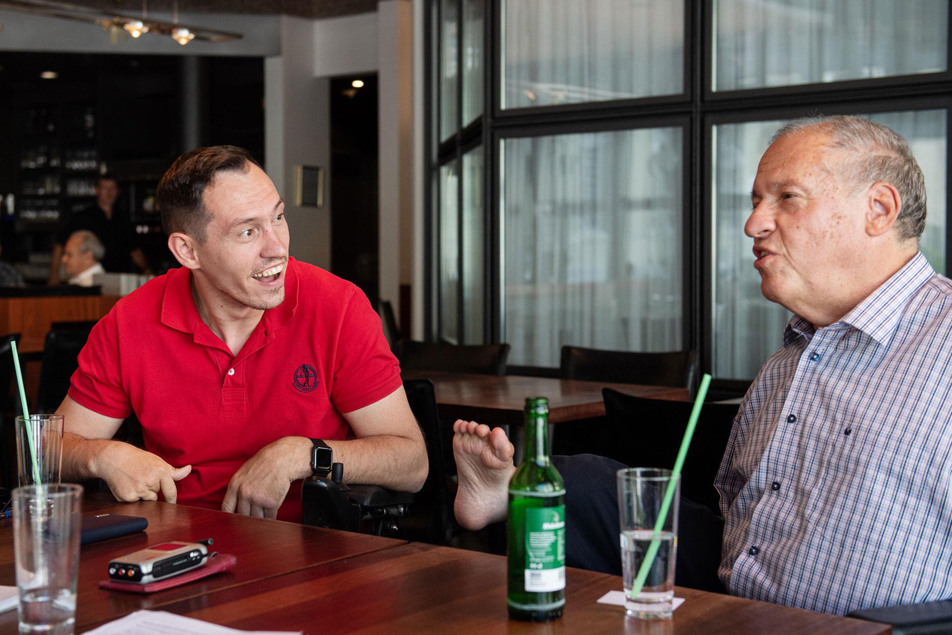 Islam Alijaj et Christian Lohr discutent, assis à une table dans un café.