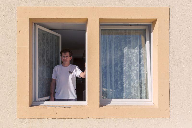 Ein Mann schaut aus dem Fenster seiner Wohnung.