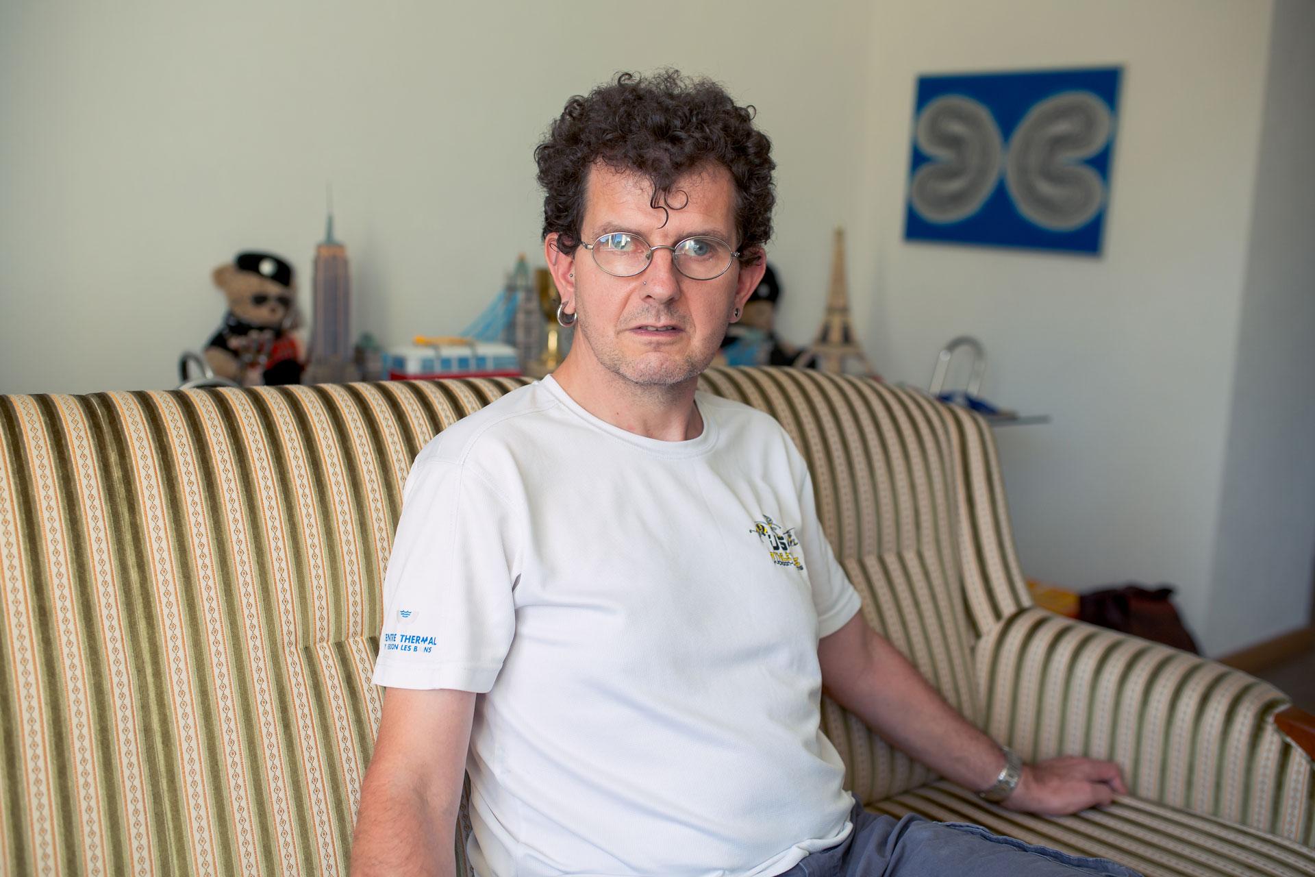 Sébastien Vulliemin, assis sur son canapé.