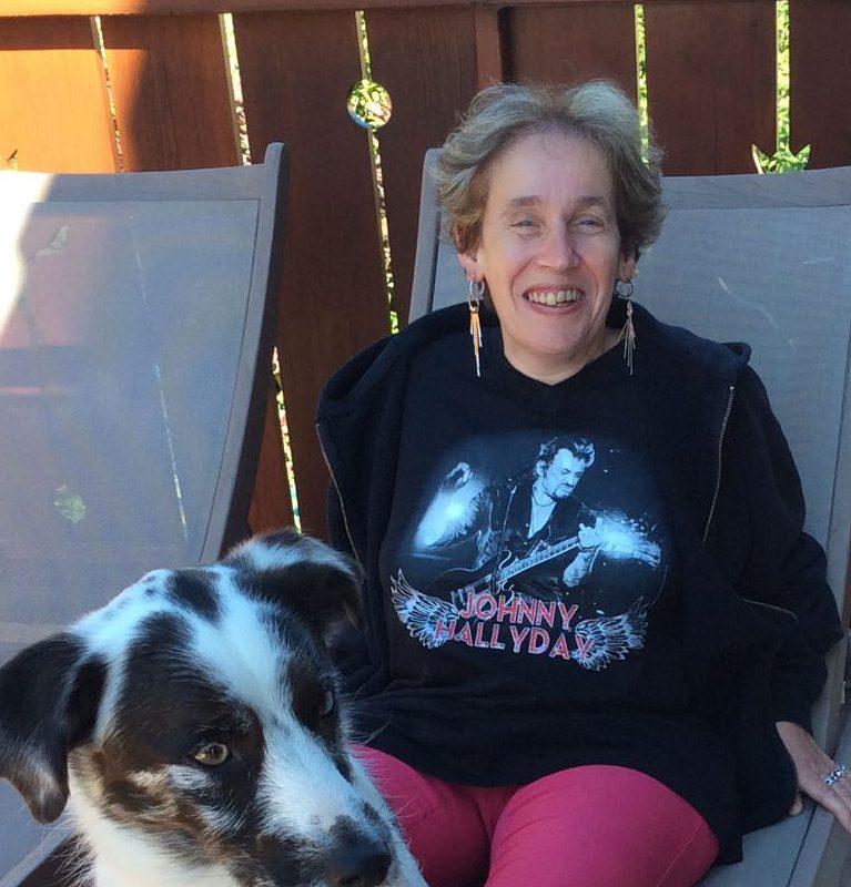 Eine Frau sitzt mit einem Hund auf einem Liegestuhl auf der Terrasse.