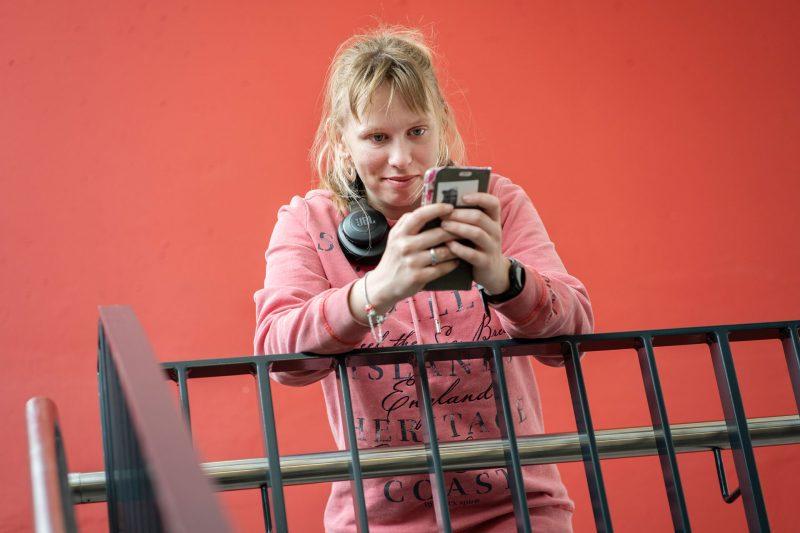 Une jeune femme est accoudée à une barrière et regarde son téléphone. Elle porte un pull rose et des écouteurs pendent autour de son cou.