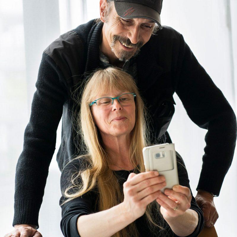 Un couple de parents regarde un téléphone. La femme est assise à une table et l'homme est debout derrière elle.