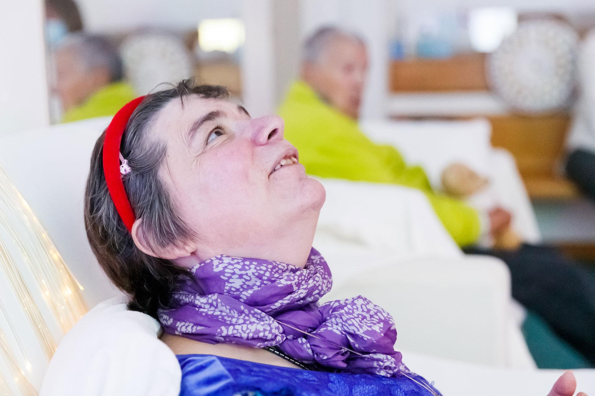 Eine Frau mit geistiger Behinderung schaut an die Decke, ausgestreckt auf einem Schaukelstuhl. Im Hintergrund sehen wir eine weitere Frau auf einem Sofa sitzen