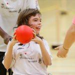 Amélie Broch se prépare à lancer la balle, assise dans un fauteuil roulant.