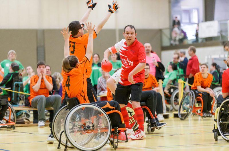 Ein Rafroballspieler mit dem Ball in der Hand bewegt sich zwischen zwei gegnerischen Spielern, die versuchen, ihn zu blockieren. Einer der gegnerischen Spieler steht und der andere sitzt im Rollstuhl