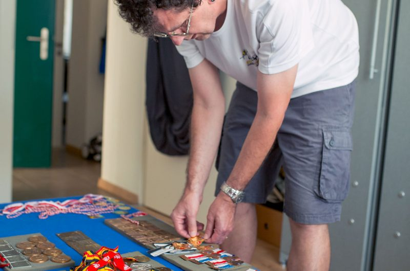 Ein ehemaliger Marathonläufer breitet viele gewonnen Medaillons vor sich aus.