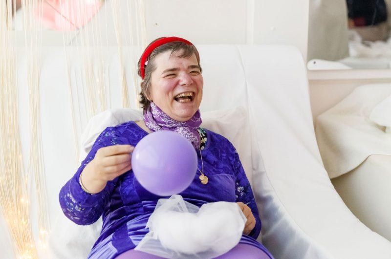 Mireille Holzer est assise dans un fauteuil à bascule. Elle tient un ballon violet dans la main droite et un sachet avec de la ouate dans la main gauche.