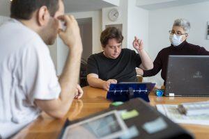 Deux hommes sont assis à une table avec un ordinateur et une tablette. Une femme se tient debout près d'eux.