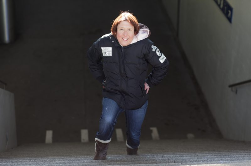 Une jeune femme se tient sur les marches d'un escalier.