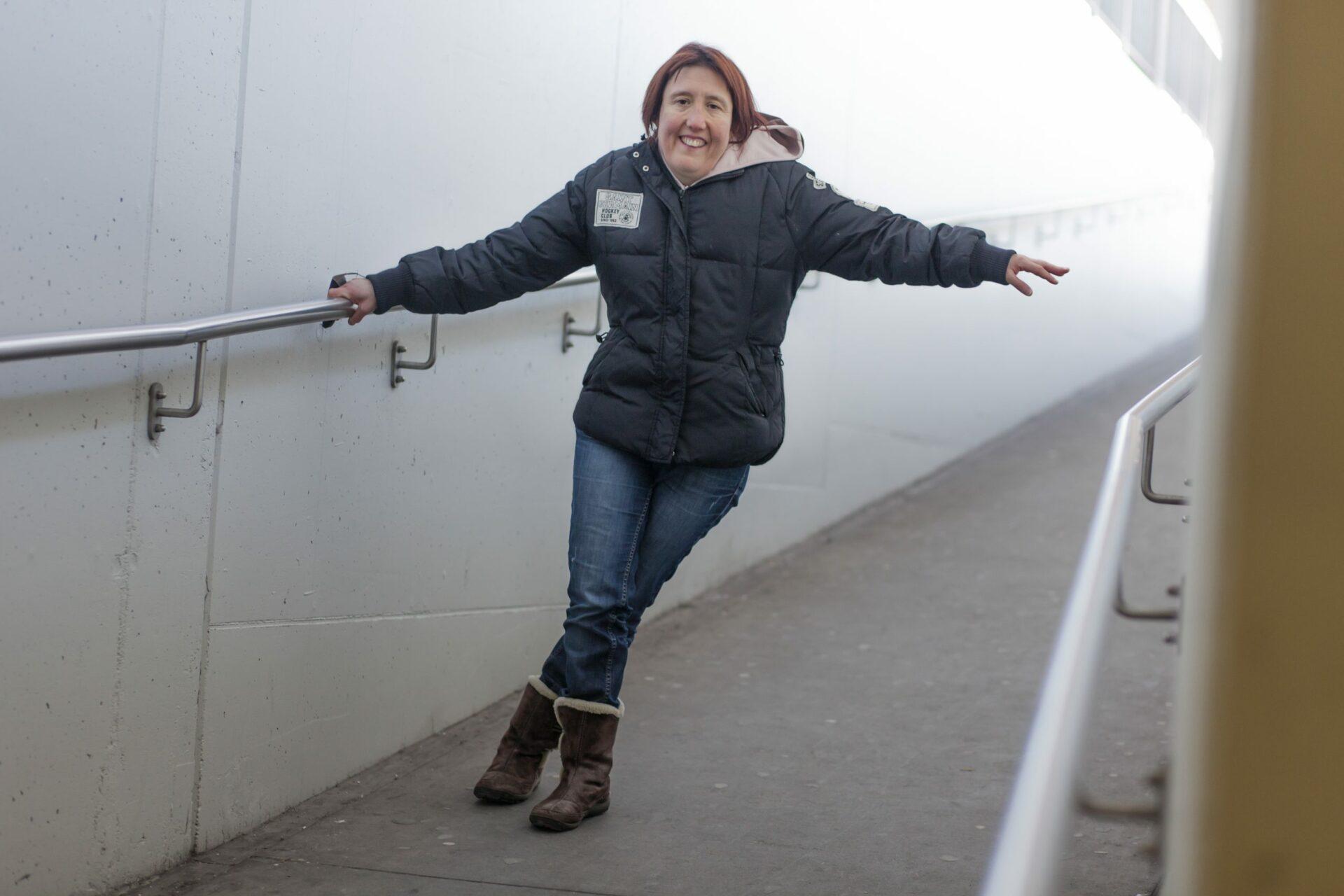 Une femme se tient à une rampe et sourit.