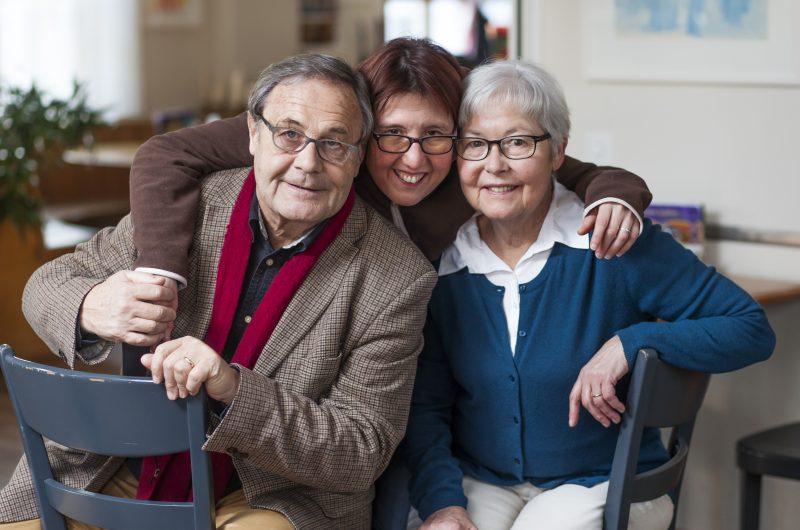 Une jeune femme enlace ses deux parents.