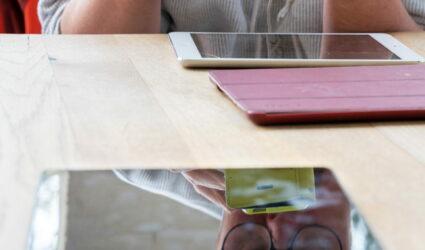 Mann mit Handy reflektiert im Bildschirm eines Tablets