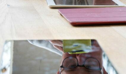 Reflet, dans l'écran d'une tablette, du visage d'un homme