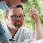 Zwei Männer konzentriert am Tisch.