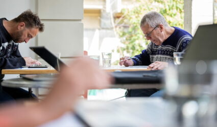 Zwei Männer lesen an einem Tisch