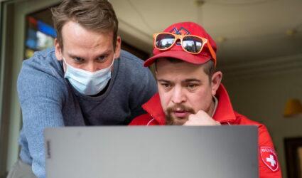 Zwei Männer hinter dem Bildschirm eines Laptops.
