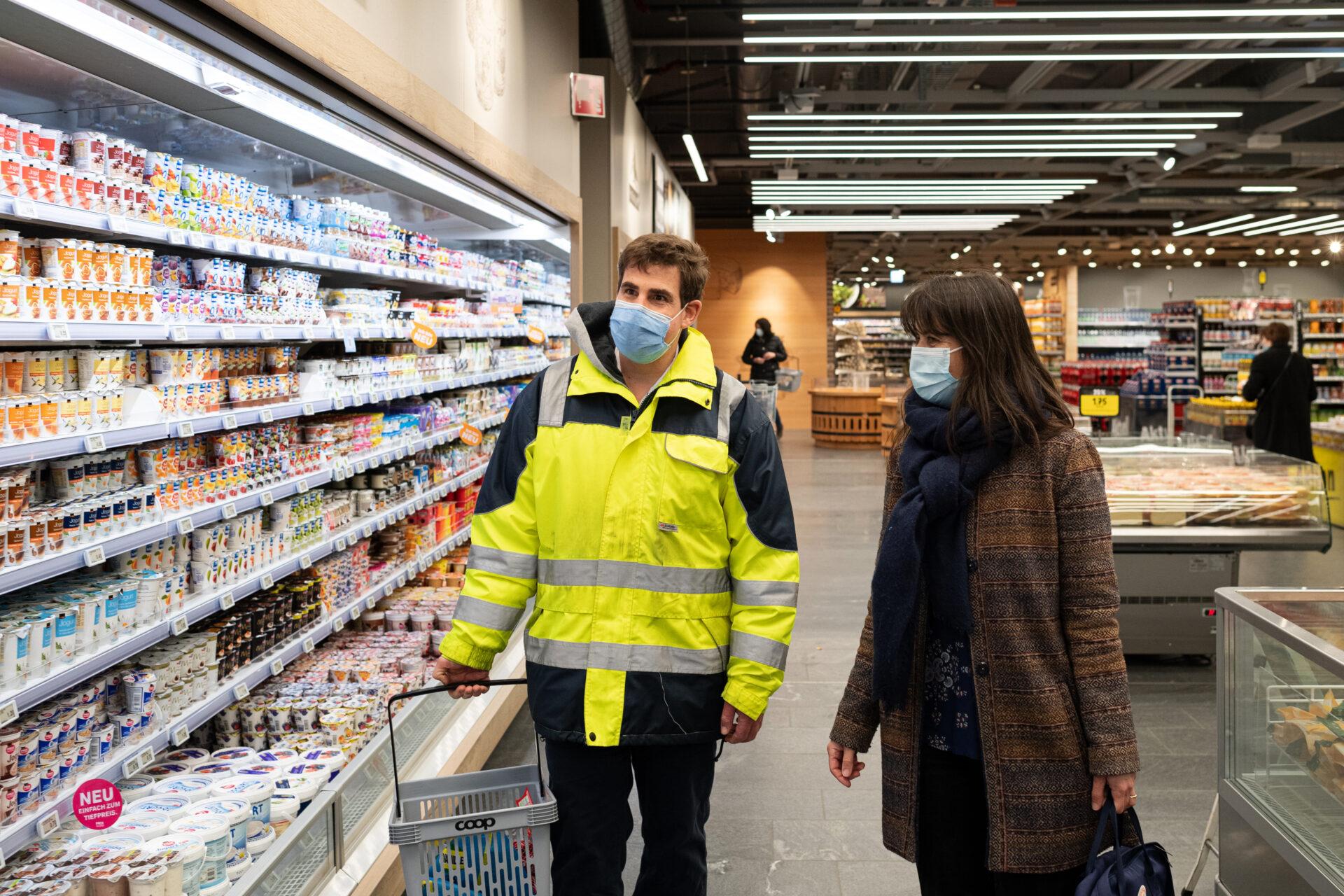 Un homme et une femme se tiennent au rayon laitier d'un supermarché.