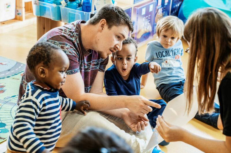 Des enfants et un homme regardent un tableau que leur tend et une éducatrice. Ils montrent du doigt quelque chose sur le tableau