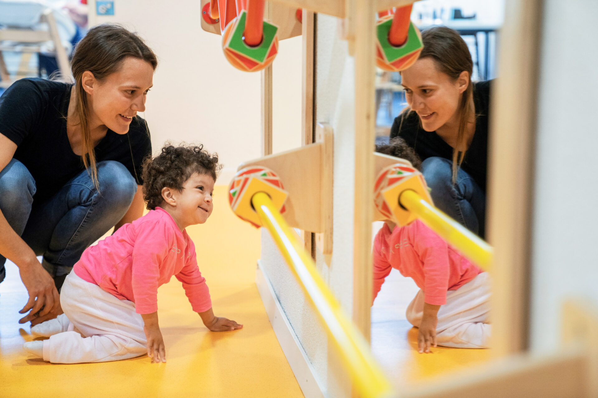 Un enfant et une éducatrice se regardent dans le miroir.
