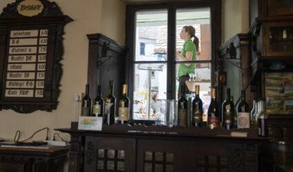 Une jeune femme se tient derrière la fenêtre d'un restaurant.