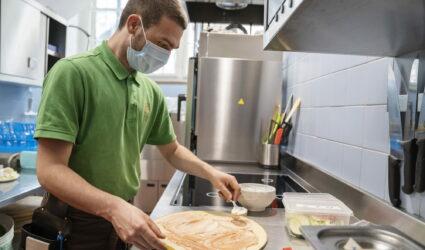 Un jeune homme prépare une pizza.