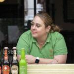 Eine junge Frau im grünen T-Shirt schaut aus dem Fenster der Beiz.