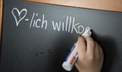 Quelqu'un écrit Herzlich Willkommen sur un tableau noir