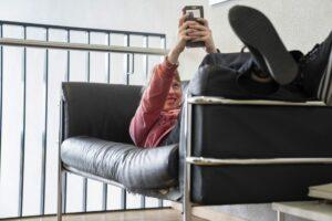Eine junge Frau surft auf ihrem Handy, während sie auf einem Sofa liegt.
