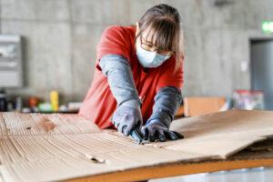 Une femme coupe un carton