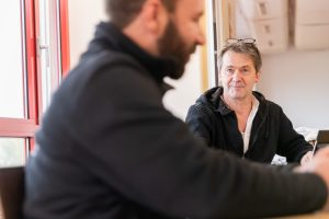 Sylvain Abraham und Yann Lhéridaud sitzen an einem Tisch. Der Coach, die Brille auf dem Kopf, hört mit einem Lächeln zu.