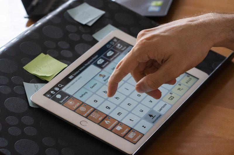 Une main clique sur un clavier affiché sur un écran de tablette. L'écran affiche également des propositions de mots.