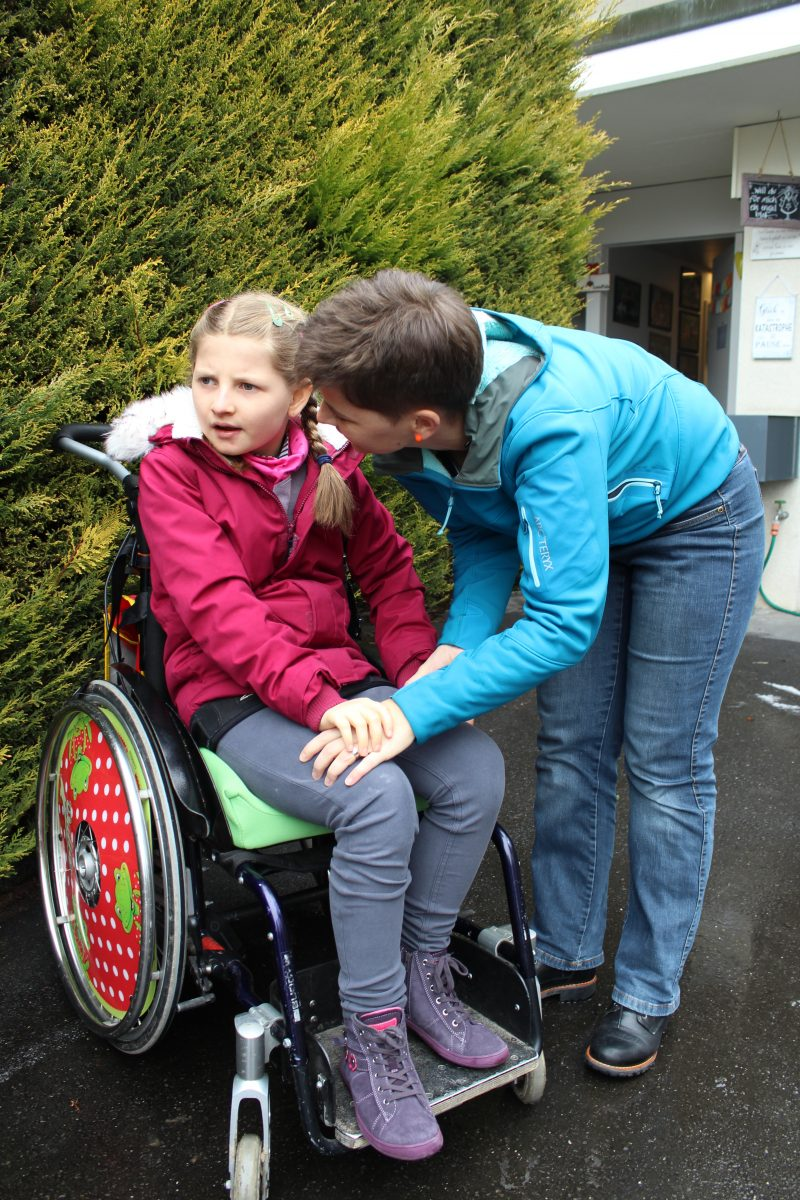Une jeune fille est assise dans un fauteuil roulant. Sa mère est penchée vers elle.
