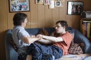 Un jeune homme est allongé sur le canapé. Il tient les mains de sa mère, elle aussi sur le canapé.
