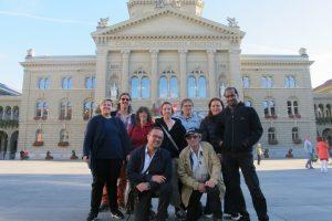 Un groupe de neuf personnes fait face à l'objectif sur la place du Palais fédéral