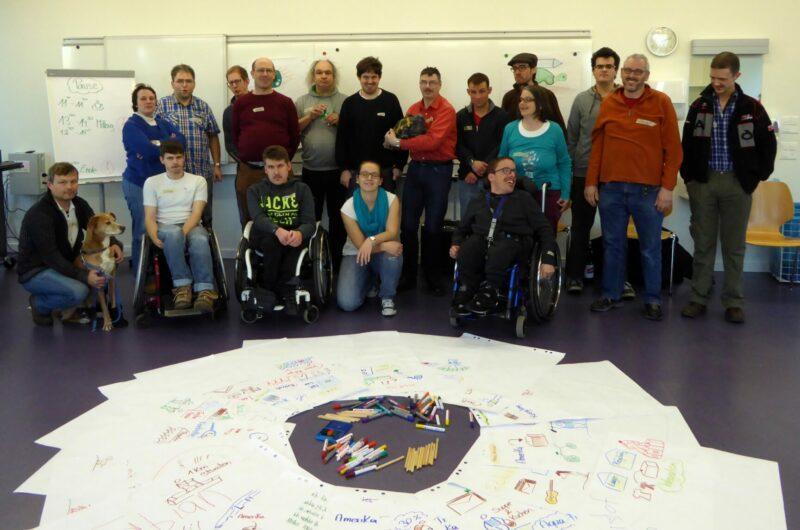 Eine grosse Gruppe von Menschen lächelt zur Kamera. Einige sitzen in Rollstühlen, andere stehen oder haben sich hingesetzt. Vor ihnen wird ein Kreis aus Flipchart-Blättern mit Stichworten und Piktogrammen auf den Boden gelegt.