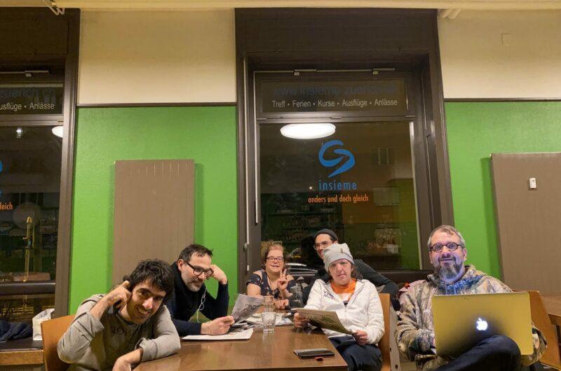 Sechs Personen sitzen um einen Tisch und schauen in die Kamera. Einige halten einen Laptop oder eine Zeitung in der Hand. Auf dem Fenster im Hintergrund steht das insieme-Logo.